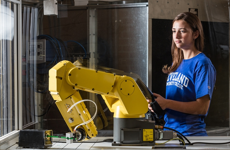 Female student operating robotic arm.